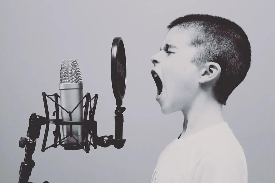 ein Kind mit weit offenem Mund vor einem Mikrophon
