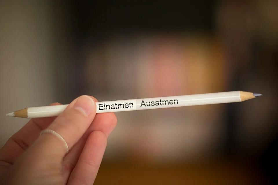 eine Hand hält einen Stift mit zwei Spitzen und der Beschriftung Einatmen Ausatmen